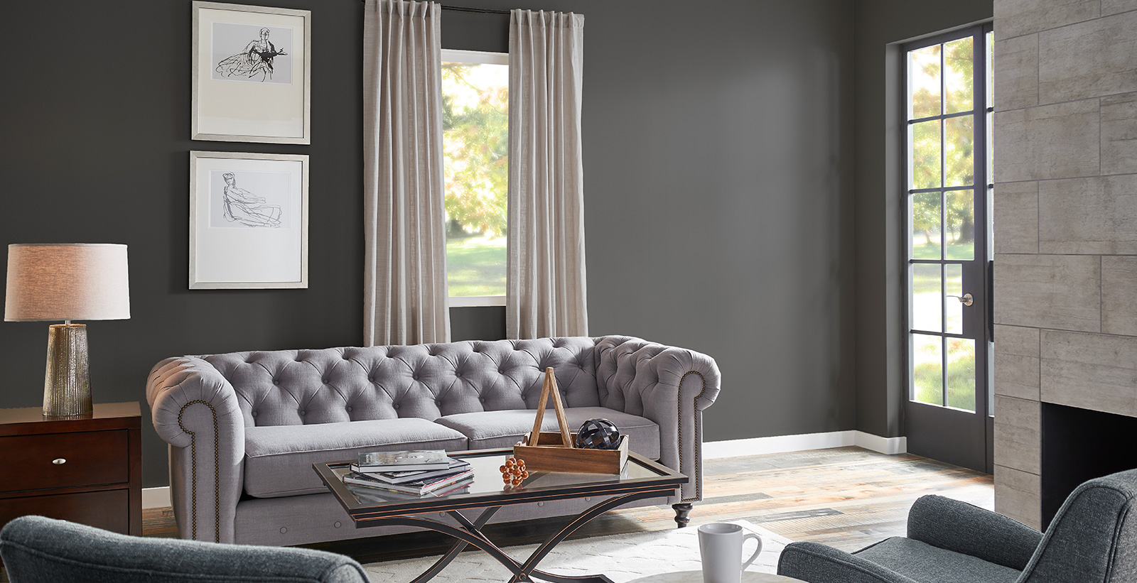 Minimal styled living room with dark gray on walls, white on trim, and light gray tufted couch