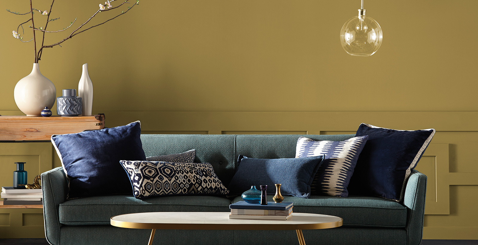 Mid-Century Modern living room with dark gold on walls, denim blue couch, navy and cream throw pillows, and metallic oval coffee table