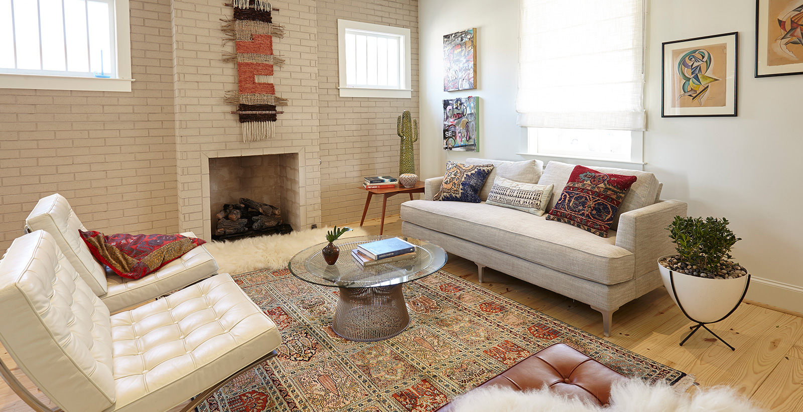 Bohemian styled living room with white on main walls, off white on brick wall with fireplace, light beige couch and cream leather chairs
