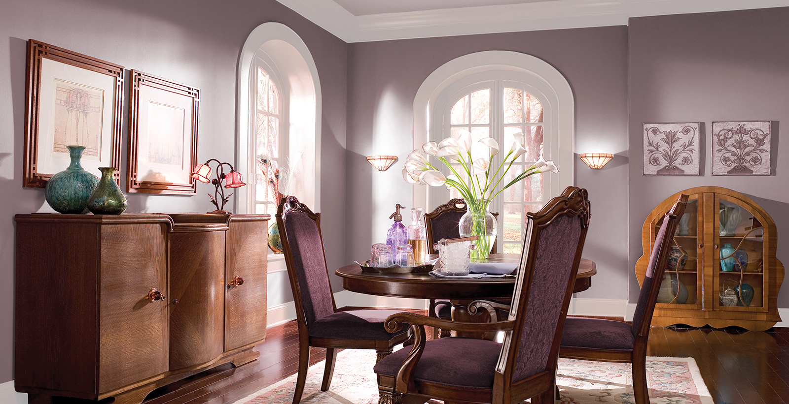 Dining room in the Art Nouveau style with mauve paint on walls, white paint on trim and pale gray on arched window trim.