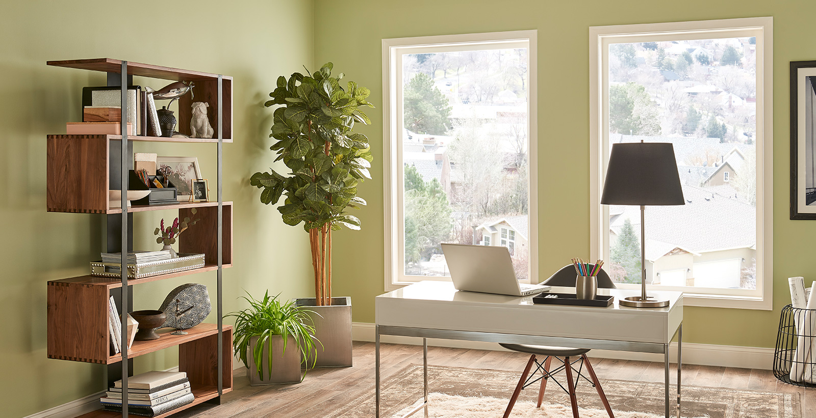 Office workspace with green walls and white trim, white desk, relaxed and calming style.
