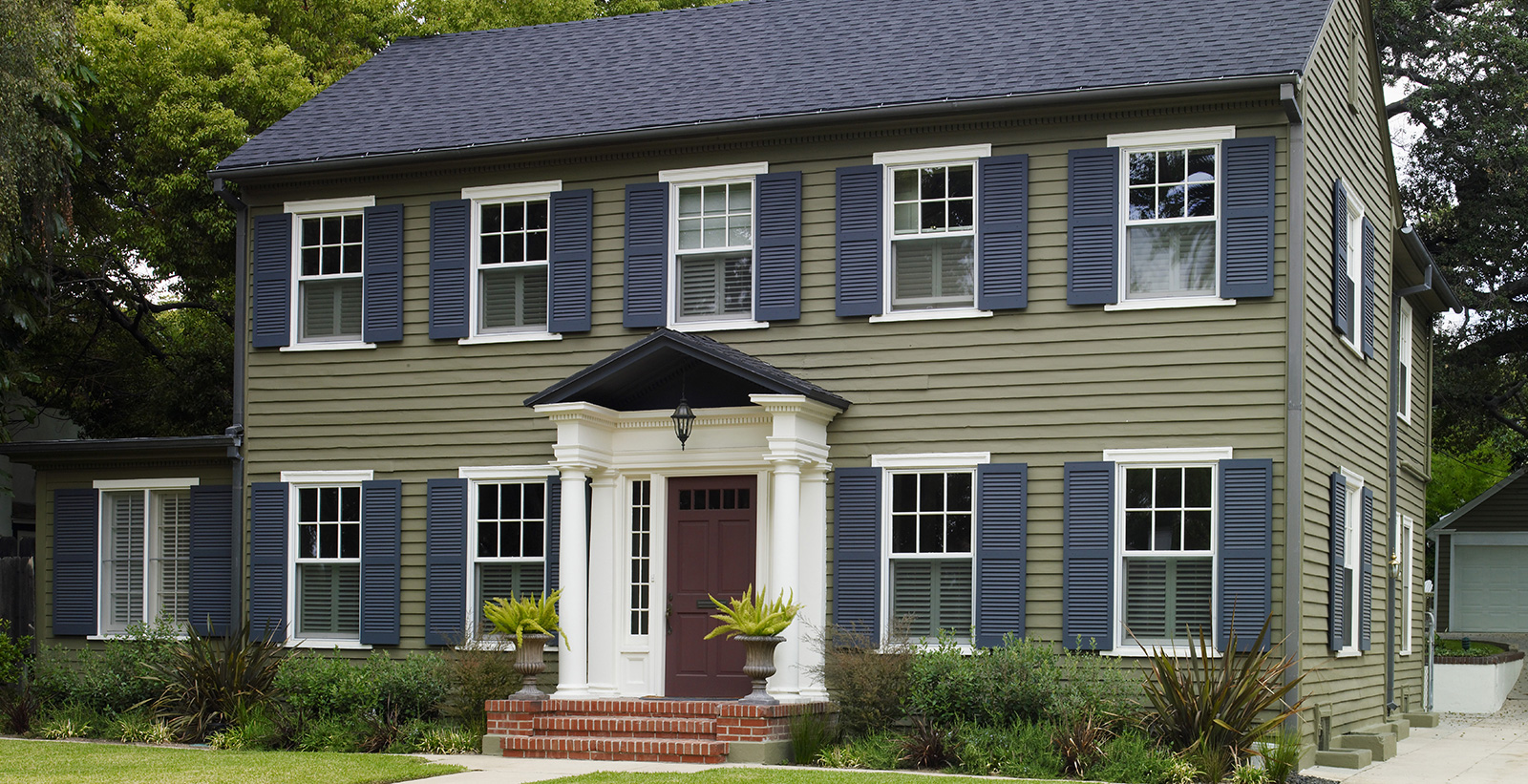 Colonial themed house with green walls, white trim, blue shutters and red door.