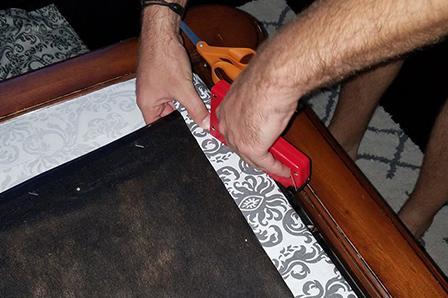 Fixation du nouveau tissu sur le siège d'une chaise avec des agrafes