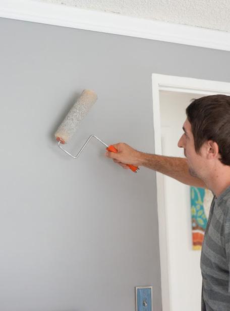 Homme peignant le mur avec un rouleau