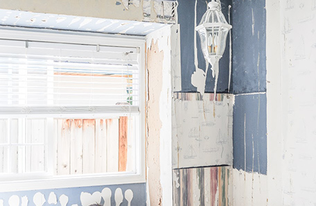 Mur de la chambre à coucher décapé montrant plusieurs couches de papier peint et de peinture