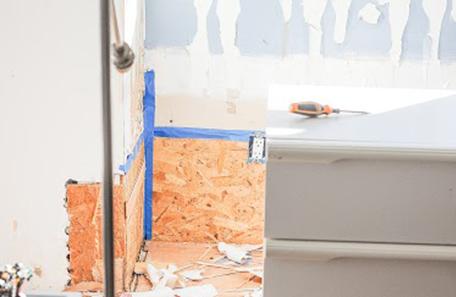 Mur de la chambre à coucher décapé montrant des panneaux de particules et du ruban adhésif