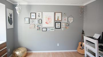 Mur fraîchement peint avec plusieurs œuvres d'art encadrées
