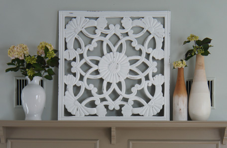 A stamped metal screen and vases of flower on top of the mantel
