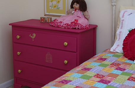 Une poupée portant une robe à dentelle, perchée sur la commode nouvellement peinte, accueille les invités.