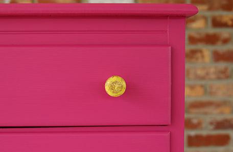 Les nouvelles poignées jaunes sont magnifiques contre la commode rose intense