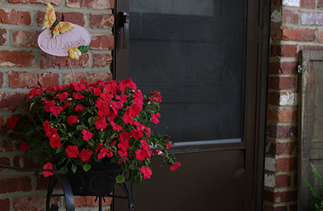 A bright red impatiens dresses up the entryway nicely