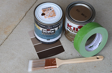 Paint brush, Behr colour chips, painter's tape, and a quart each of paint and primer