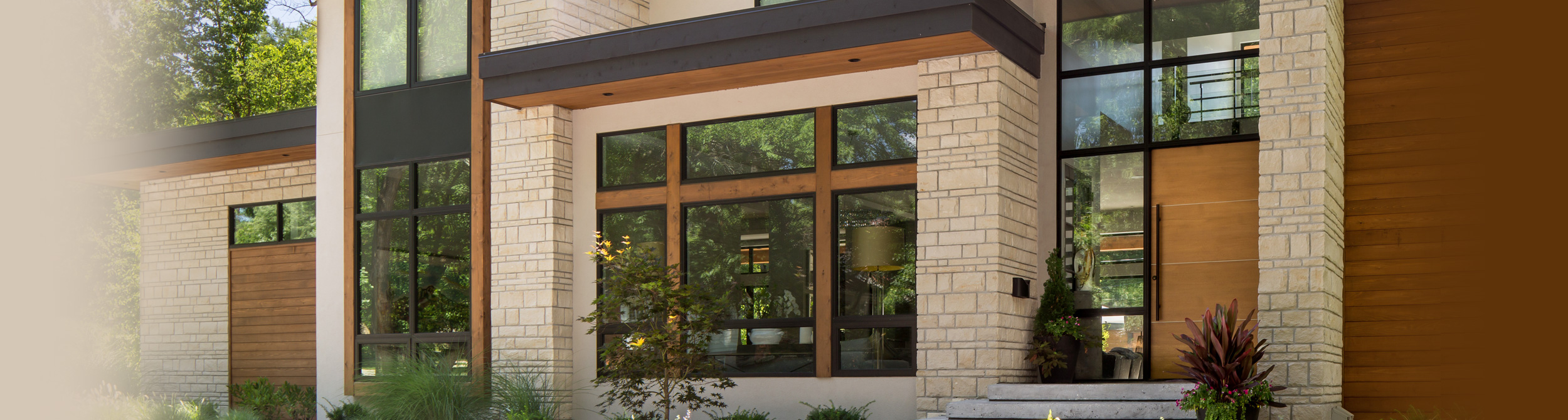 Modern brick house with expansive glass windows.