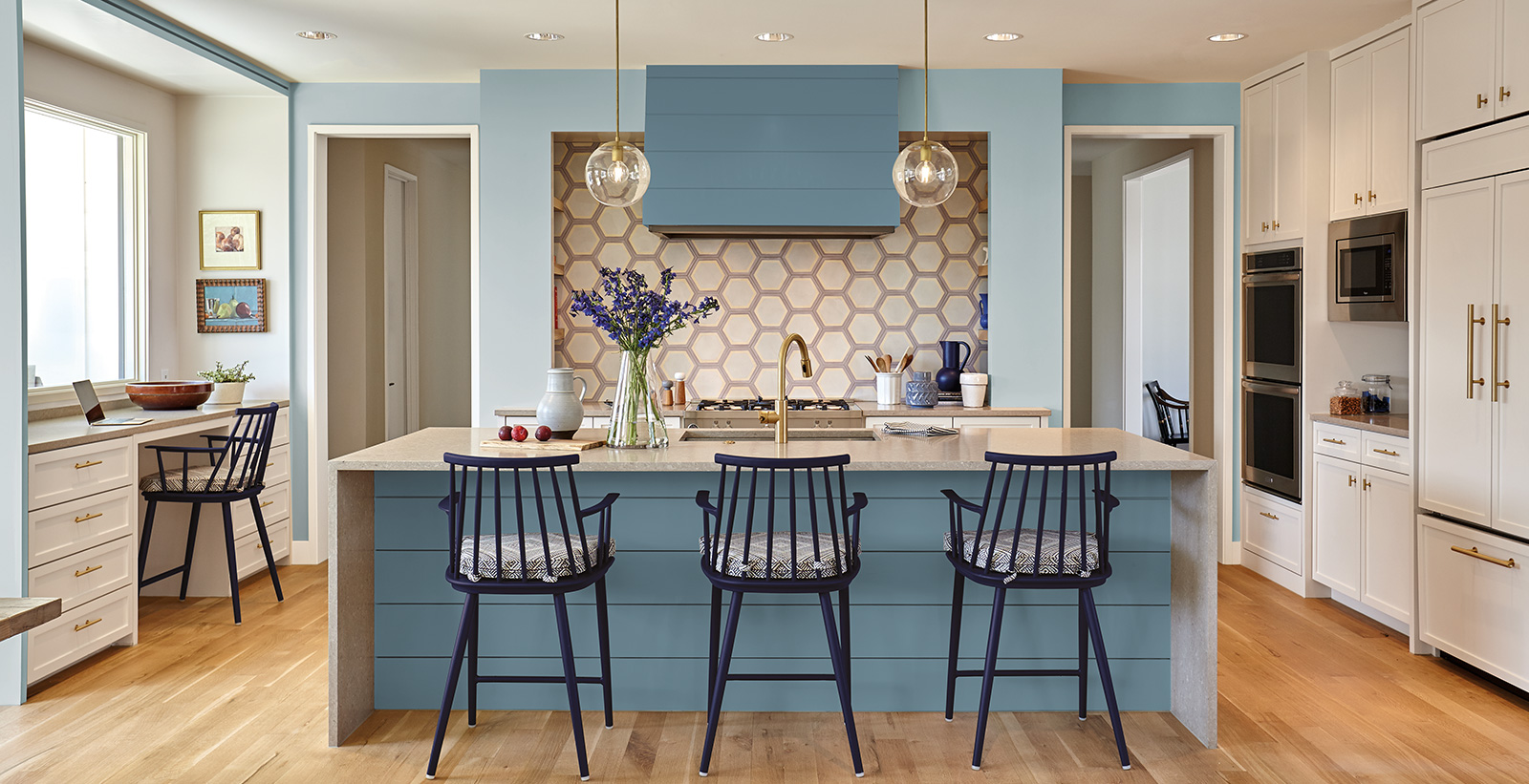Relaxed kitchen with light blue on accent wall, white on ceiling and cabinets and honeycomb backsplash