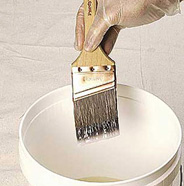 Brush being dipped in pail of paint or primer