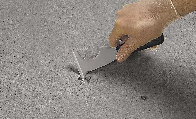 Image d'un trou dans le béton avec un outil montrant comment le fixer.