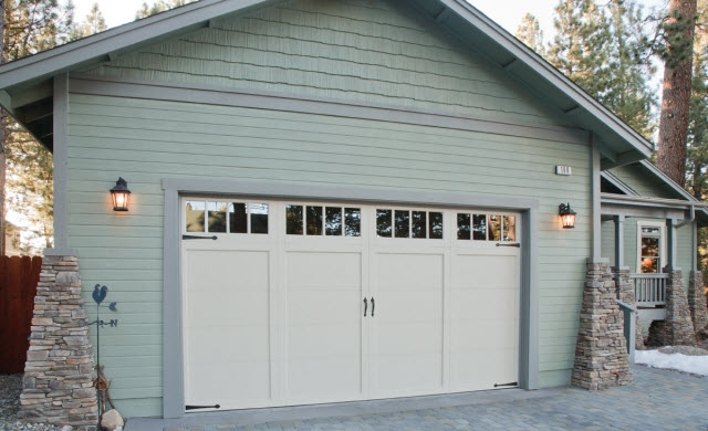 Image of exterior of a garage and garage door with teal siding.