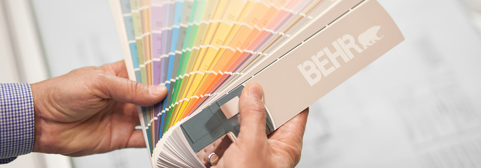 A large image of a BEHR Colour Fan Deck held by a hand.