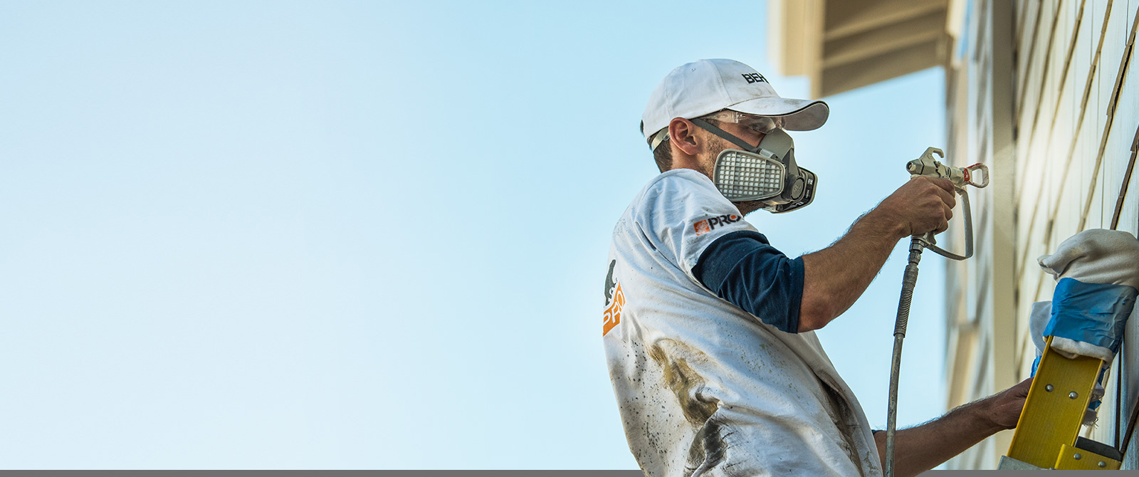 Large image of a Pro Contractor wearing a cap and shirt with Behr logo spray painting the exterior of house on a ladder.