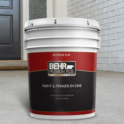A 5 gallon of BEHR Premium Plus Exterior Flat on the floor in front of a front door.