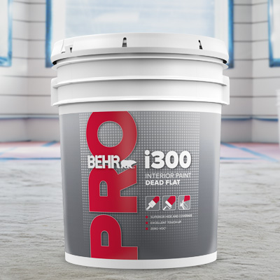 A 5 gallon of BEHR PRO i300 on the floor in front of an window.