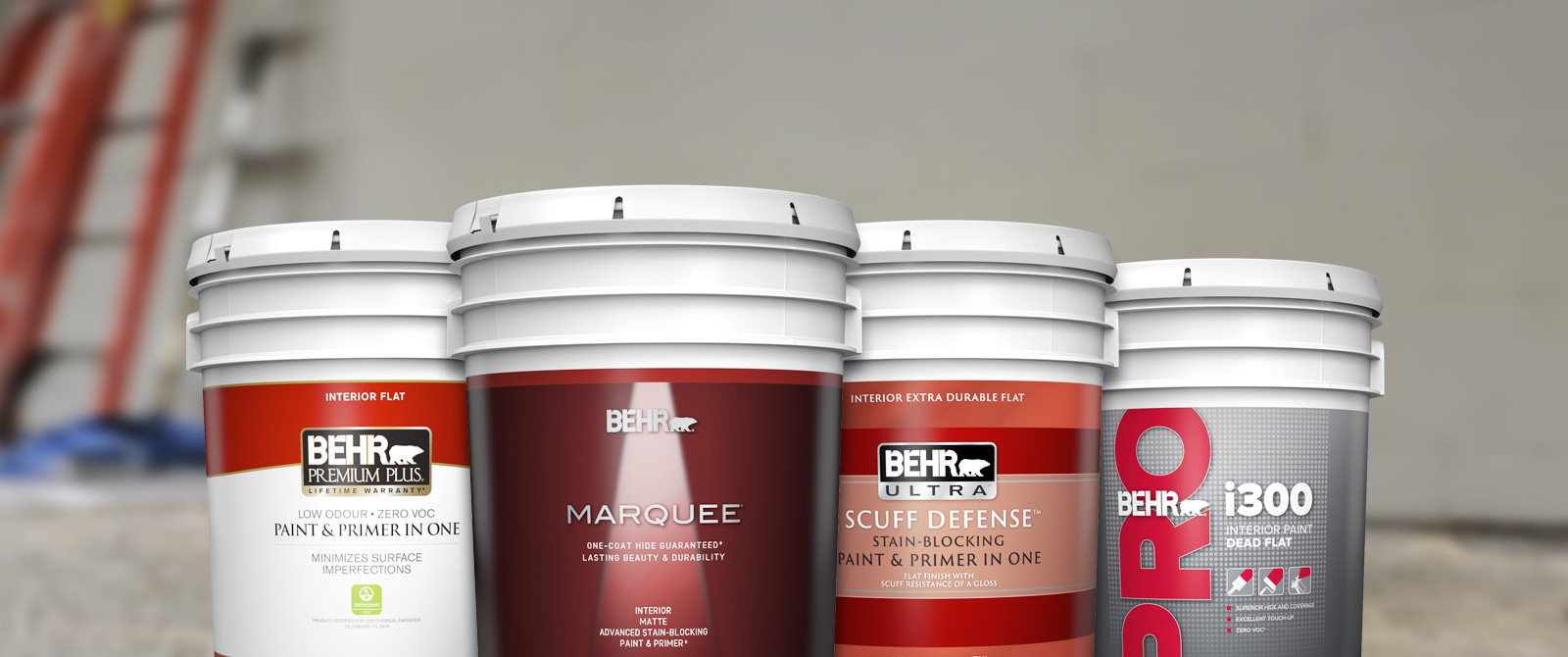 Landscape View of  a 5 gallon product cluster shot of BEHR PREMIUM Interior Flat, BEHR MARQUEE Interior Matte, BEHR ULTRA Interior Matte, and BEHR i300 Dead Flat. In the background, there is a ladder leaning on an unpainted interior wall.