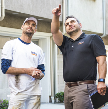 A BEHR Rep pointing at a building while a Pro Painter is looking at what he is pointing.