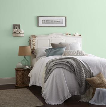 Un lit avec une tête de lit blanche appuyée contre un mur vert