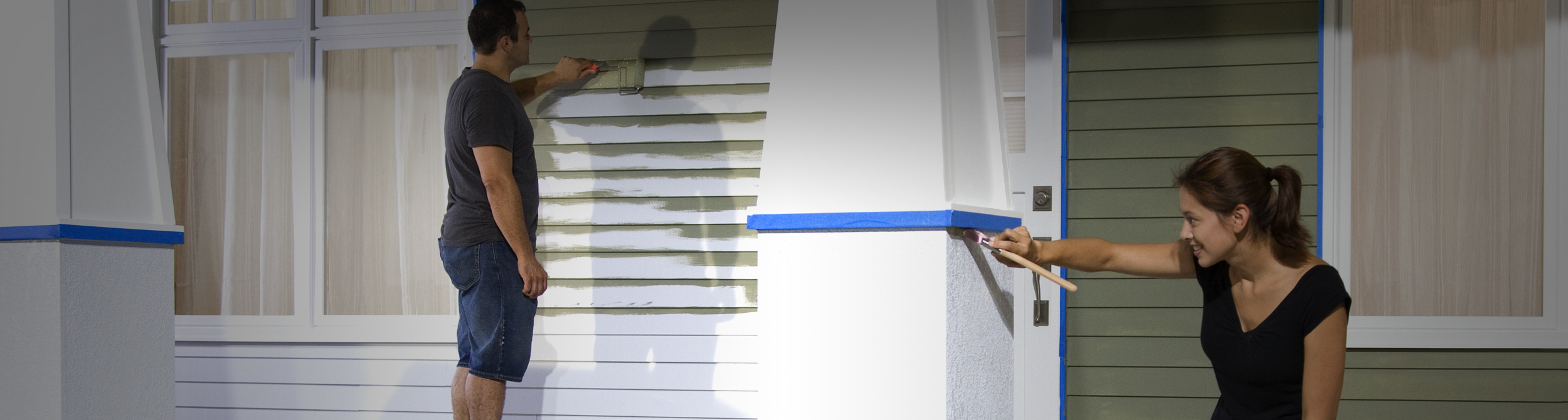 Man and woman painting house exterior.