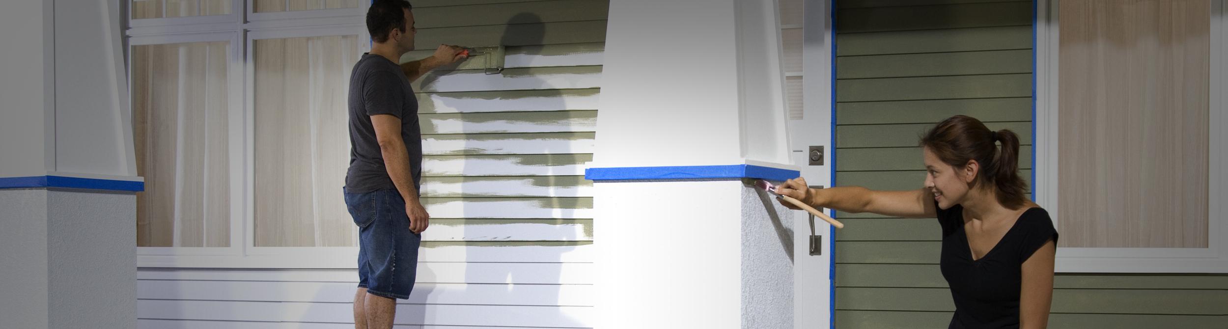 Un homme et une femme qui peinturent l'extérieur d'une maison.