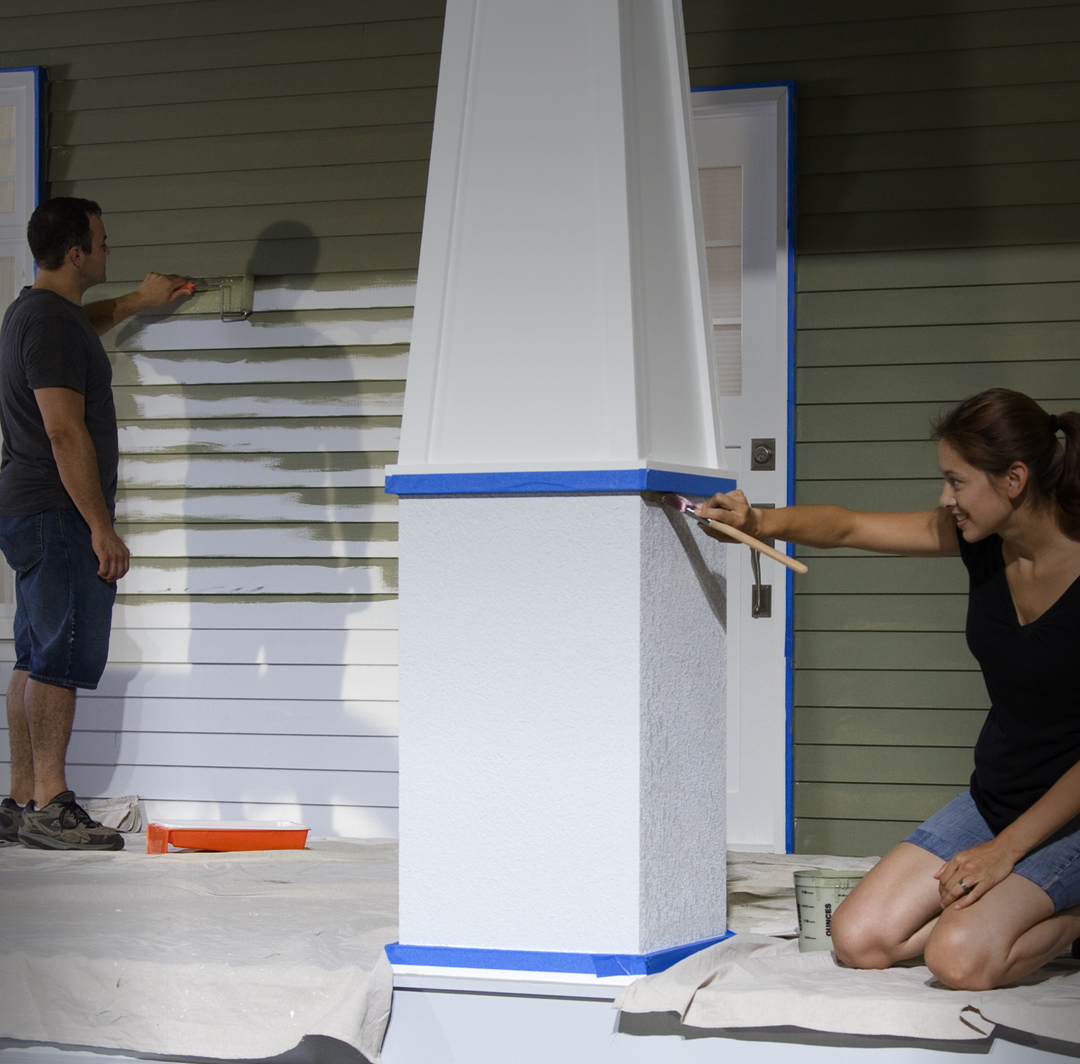 Mobile-sized image of man and woman painting house exterior.