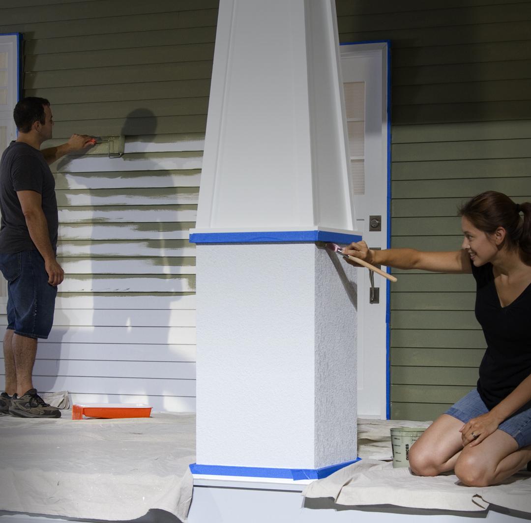 Image version mobile d'un homme et une femme qui peinturent l'extérieur d'une maison.