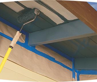 Teindre le dessous d'une terrasse extérieure avec un rouleau à rallonge