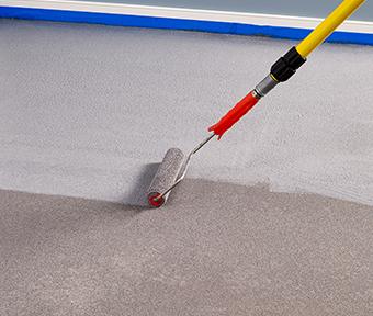Applying granite grip to floor with roller