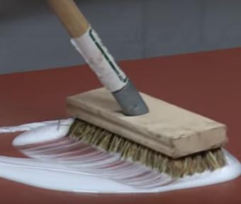 Brosse frottant une substance blanche semblable à de la peinture sur un plancher