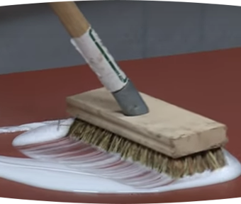 A brush scrubbing a white paint like substance onto flooring