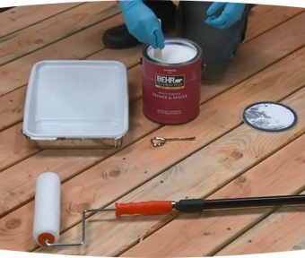 A person kneeling down with paint brush in hand and paint roller and paint can aside them