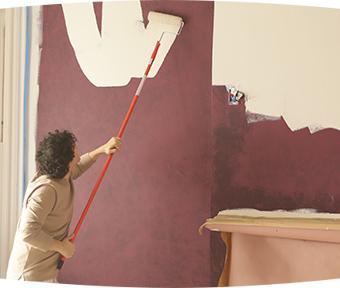 Une personne peint un mur à l'aide d'un  rouleau à rallonge