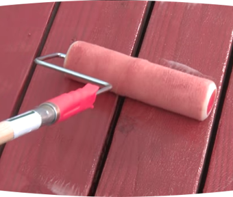 Paint roller painting a wood deck