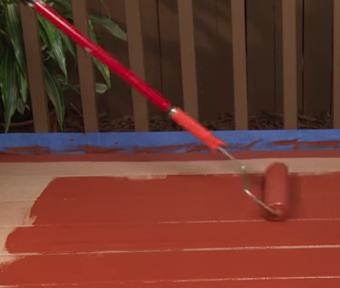 Une personne appliquant de la teinture sur une surface de bois composite avec un rouleau