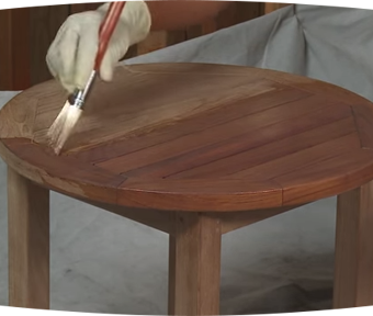 Person staining wood table with small paint brush