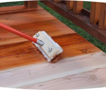 Un pinceau utilisé pour l'application d'une teinture sur une terrasse