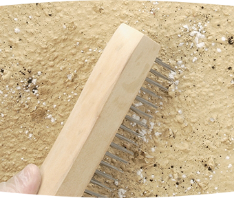 Person holding a comb like tool against surface
