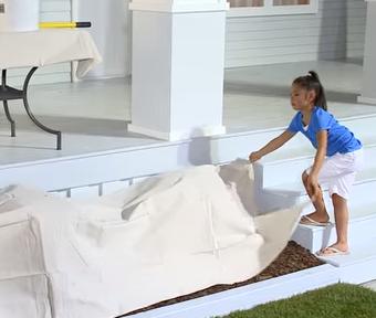 Un enfant dépose une bâche sur l'aménagement paysager en vue de travaux de peinture à l'extérieur