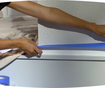 Person applying blue painter's tape to a wall