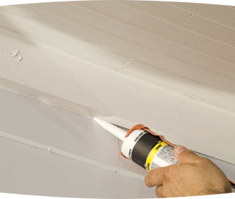 Person applying a gel to the exterior of a house between the siding and the floor