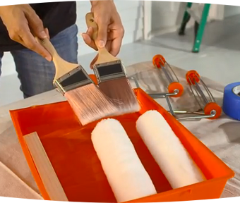 Person holding a paint brush in each hand and two paint rollers in a tray