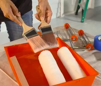 Personne tenant un pinceau dans chaque main et deux rouleaux de peinture dans un bac de peinture