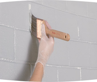 A person painting a brick wall with a paint brush