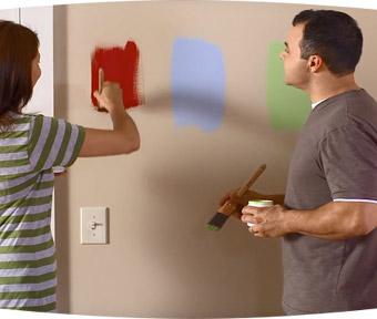 Un homme et une femme testant différentes couleurs de peinture sur le mur